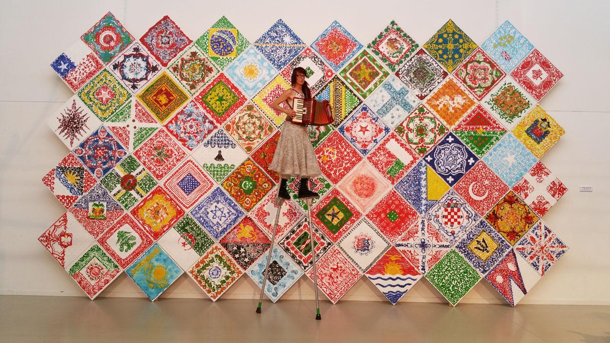 Flags of the world, wall presentation, 620 x 360 cm, CBK Oost, 2016, tijdens Ontroerwoud van Wim Vonk, organisatie St. Polderlicht. Dagmar Chittka (Rauher Engel) on stelts.